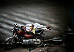 A man sleeps on his bike in New Delhi, India, in May 2009.