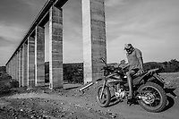 PAULISTANA, BRAZIL - FEBRUARY 04, 2014: Francisco Hortencio Rodrigues, 45, a farmer whose lands have been over taken by the Transnordestina railway project, looks on as he sits on his bike beneath the 150 ft high concrete pillars of an abandoned bridge, built on his property on February 04, 2014 near Paulistana, Piaui province, in Northern Brazil. Representatives of the project offered Mr Rodrigues 30,500 Reals (13,000USD) for his land, but he is yet to see any of it. The Transnordestina, a 1,400-mile railroad project which a steel company began building in 2006 in northeast Brazil, offers a view into the pitfalls plaguing projects big and small across Brazil. Intended to be finished in 2010 at a cost of about $1.8 billion, the railroad is now expected to cost at least $3.2 billion, with ample financing from state banks, and be completed sometime around 2016. Long stretches along the routes where freight trains were already supposed to be running now stand completely deserted. Wiry vaqueiros, or cowboys, herd cattle in the shadow of futuristic railroad bridges with massive concrete pillars towering 150 feet above parched valleys. <br /> <br /> Daniel Berehulak for The New York Times