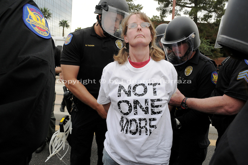 Phoenix, Arizona. April 25, 2012 - Phoenix Police officers arrest Amy McMullen, one of the six protesters who blocked Central Avenue. About 500 people protested the controversial law on the same day U.S. Supreme Court justices heard legal arguments on the Arizona vs. United States case. At the end of the march, six activists blocked Central Avenue by sitting in the middle of the street. They all were arrested by the Phoenix Police Department and taken to the Fourth Avenue County Jail. Photo by Eduardo Barraza © 2012