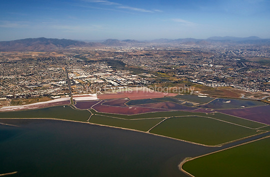 Aerial view of salt evaporation ponds in San Diego Bay, California. Salt evaporation ponds are shallow man-made ponds designed to produce salt from sea water. The seawater is fed into large ponds and water is drawn out through natural evaporation which allows the salt to be subsequently harvested (wiki 2009)