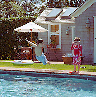 A young boy throws himself into the outdoor swimming pool whilst his brother watches from the poolside
