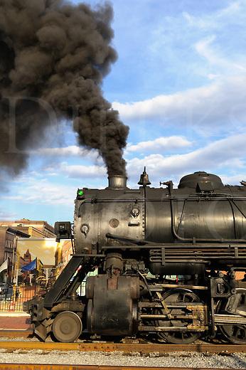 Steam locomotive sitting at the station, a fire breather making thick black smoke while stopped at rest, Cumberland, Maryland.