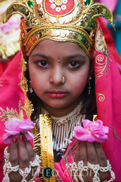 A young girl dressed elaborately in a festive costume during a holy procession in Pushkar; Pushkar is one of the five sacred pilgrimage sites for devout Hindus, Pushkar, Rajasthan, India --- Model Released