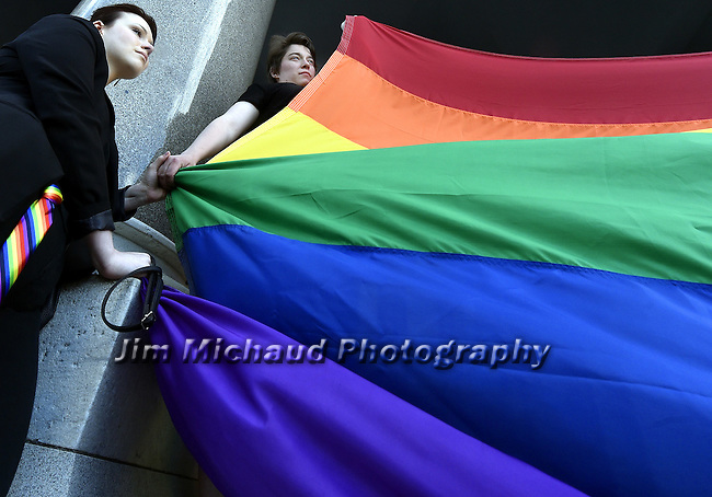Christy Matthews of Bristol,  left, and Alex Cross of Watertown, hold hands as they participate in a vigil for the victims of the Orlando mass shooting, Sunday evening, June 12, 2016, on  the north steps of the State Capitol in Hartford. (Jim Michaud / Journal Inquirer)