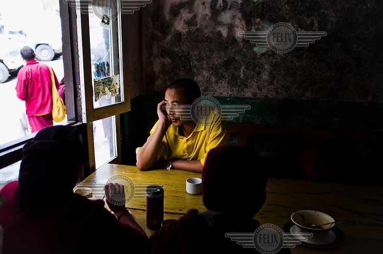 Buddhist monks sip tea in a restaurant in Tatopani, a small town on the Chinese border.
