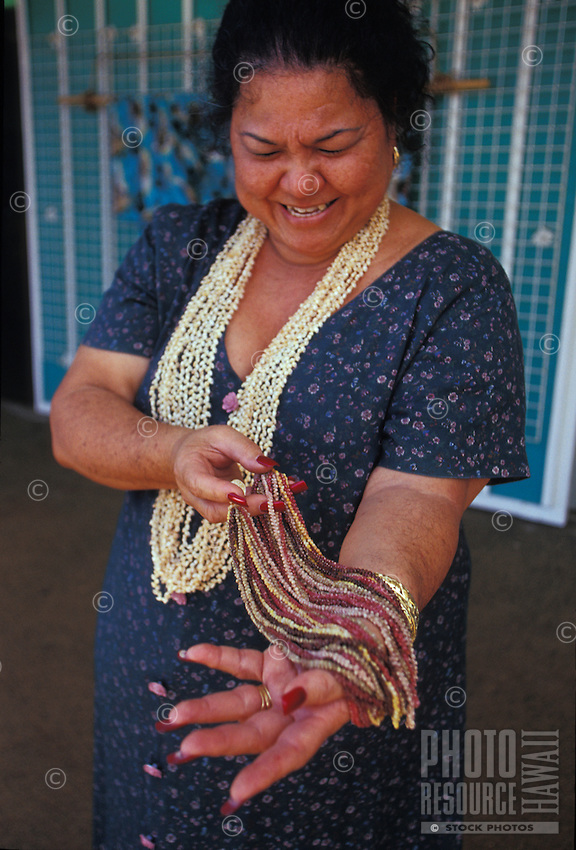 Rare and valuable Niihau Shell Necklace of Kahelelani shells held by Hawaiian woman
