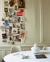 An assortment of postcards and photographs has been stuck onto the wood panelling of this dining area