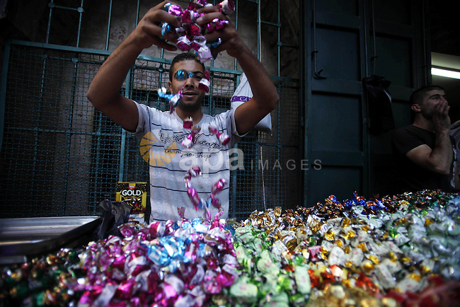 A Palestinian displays traditional sweets in the old city of Jerusalem during the fasting month of Ramadan on July 31, 2012. Photo by Saeed Qaq