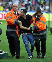 Safety stewards remove a Manchester City supporter who invaded the pitch after Raheem Sterling of Manchester City scored his goal during the Premier League match between Swansea City and Manchester City at The Liberty Stadium in Swansea, Wales, UK. Saturday 24 September 2016