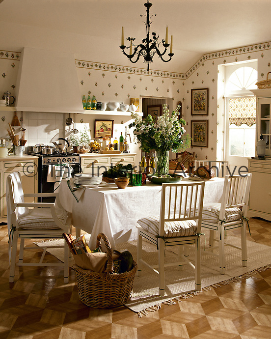 A kitchen dining room with white units, floral pattern wallpaper and a wooden floor. A table and white painted chairs are placed in the centre of the room.