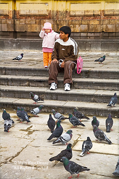 Little girl holds her hat standing beside dad sitting on steps in main plaza with pidgeons in Lima, Peru