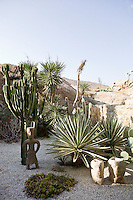 A cactus garden covered with gravel and decorated with small stone sculptures