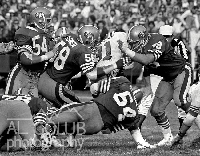 """San Francisco 49ers vs. Atlanta Falcons at Candlestick Park Sunday, November 8. 1981.  49ers beat Falcons 17-14..San Francisco 49er Line Backer Craig Puki (54), Keena Turner (58), Jim Stuckey (79) and Jack """"hacksaw"""" Reynolds (64) gang tackle Atlanta Falcon Running Back William Andrews (31)...Photo By Al Golub/Golub Photography."""