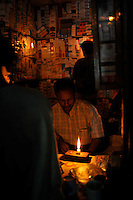 A pharmacy is lit by candle-light in the center if the Burmese capital, Rangoon, Dec 2008. Power is one of many basic commodities in short supply in the country.