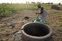 BURKINA FASO Kaya, diocese bank gives micro loan for agriculture and income generation, woman irrigates maize field /  BURKINA FASO Kaya, Bank der Dioezese Kaya vergibt Mikrokredite fuer Kleinunternehmer und Farmer zur Einkommensfoerderung, Frau bewaessert Maisfeld