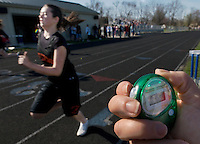 Judge check her stop watche at the finish line of a high school track meet.