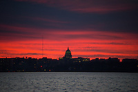 The Wisconsin State Capitol is silhouetted against the Lake Monona sunset in a view from Madison's Olbrich Park on Wednesday, December 10, 2015 in Madison, Wisconsin