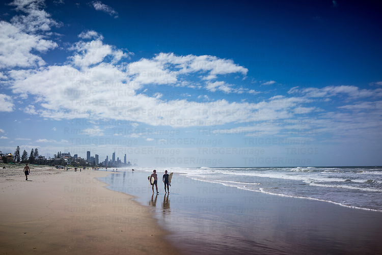 Two young male surfers on the beach at the Gold Coast in Australia