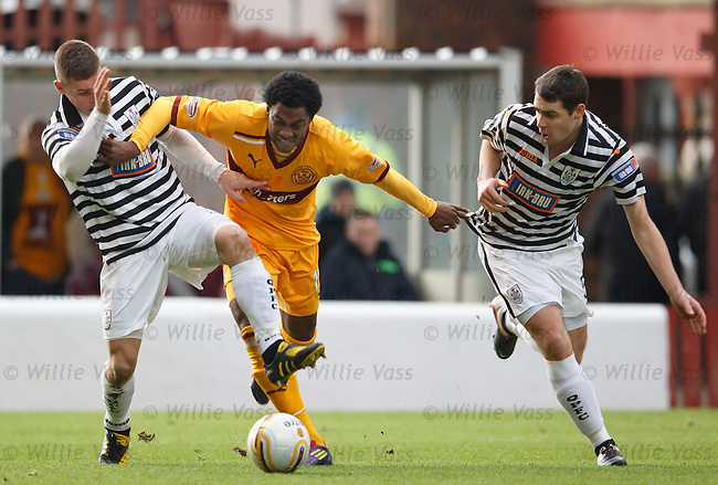 Omar Daley uses his strength to force his way past Queens defenders Darryl Meggatt and Jamews Brough to score for Motherwell