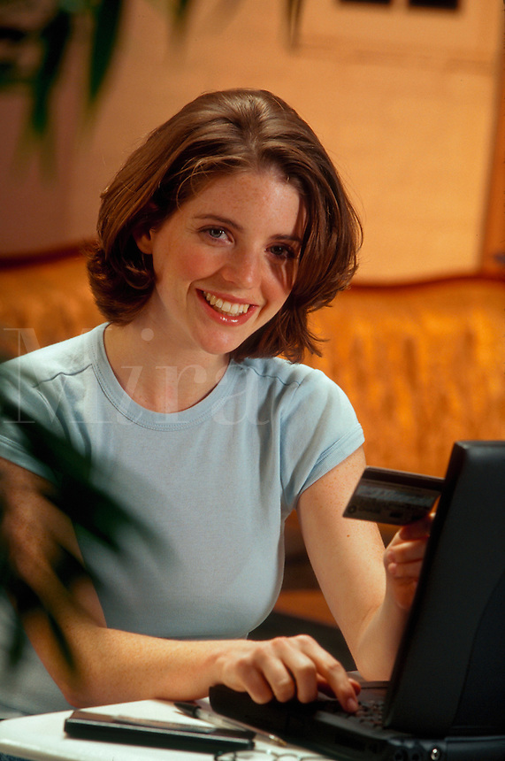 A smiling young woman working with a laptop computer.