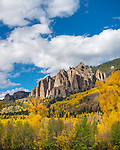 Uncompahgre National Forest, Colorado:<br /> Cliffs of the Cimarron stand abouve fall colored hillsides, San Juan Mountains