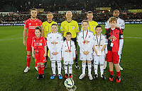 SWANSEA, WALES - MARCH 16: Children mascots with team captains Jordan Henderson of Liverpool (L) and Ashley Williams (R) of Swansea and match officials Roger East referee (C)<br />