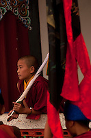 Young novice Buddhist monk, waiting with the monastery flag, for the Losar New Year ceremonial procession to begin