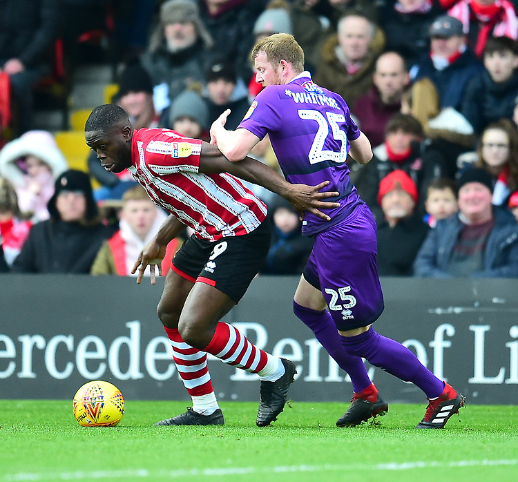 Lincoln City's John Akinde shields the ball from Grimsby Town's Alex Whitmore<br /> <br /> Photographer Andrew Vaughan/CameraSport<br /> <br /> The EFL Sky Bet League Two - Lincoln City v Grimsby Town - Saturday 19 January 2019 - Sincil Bank - Lincoln<br /> <br /> World Copyright &copy; 2019 CameraSport. All rights reserved. 43 Linden Ave. Countesthorpe. Leicester. England. LE8 5PG - Tel: +44 (0) 116 277 4147 - admin@camerasport.com - www.camerasport.com