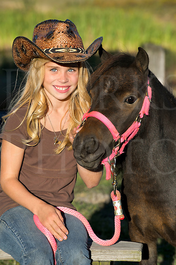 Pretty blonde girl sitting with her miniature horse, portrait of a cute cowgirl wearing a cowboy hat.