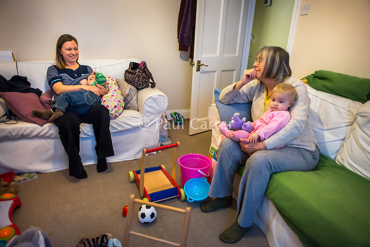 A mother sitting on a sofa in her living room breastfeeds one of her twins while her mother sits with the other one on her lap.<br /> <br /> 16 November 2012<br /> Hampshire, England, UK