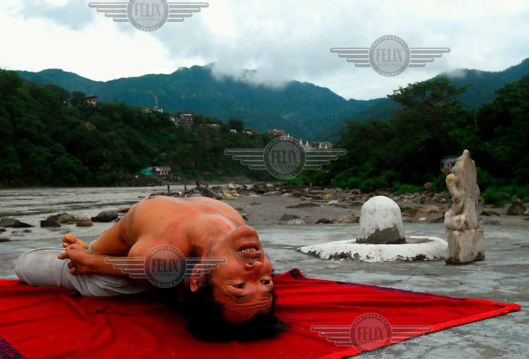 Tora, a Japanese yoga student, meditates on the banks of the River Ganges (the Ganga).