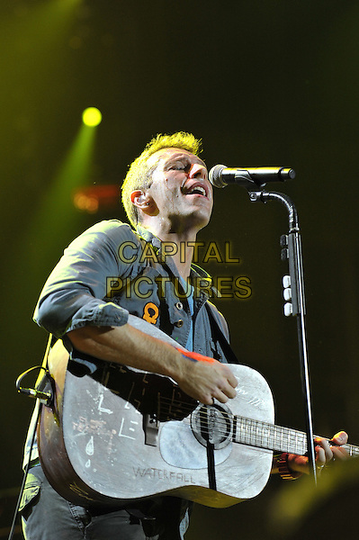 Chris Martin.Coldplay performing live in concert, O2 Arena, Greenwich, London, England. .9th December 2011.stage gig performance music half length blue jacket guitar singing  .CAP/MAR.© Martin Harris/Capital Pictures.
