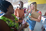 Monique Lohmeyer (right), a case manager for Church World Service, explains the use of tokens to Evanis Gatunzi (left) and Casmil Ngundakumana, refugees from Rwanda, in the Durham Farmers' Market in Durham, North Carolina. The Double Bucks program allows consumers with EBT cards to double their purchasing power.<br /> <br /> Church World Service resettles refugees in North Carolina and throughout the United States.<br /> <br /> Photo by Paul Jeffrey for Church World Service.