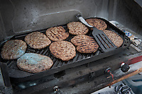 After a fire in a gas stove the firemen removed the gas containers and created a secure perimeter by sealing the area from non rescue personnel. A grease fire had started on a stove frying hamburgers.