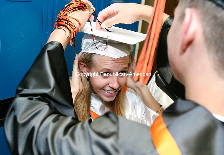 PLYMOUTH, CT, 15 June 2006- 061506BZ06- Kristie Pierzanowski gets her tassle adjusted by classmate Joseph Riggs before the start of commencement excercises at Terryville High School Thursday night. <br /> Jamison C. Bazinet Republican-American