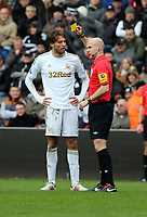 Pictured L-R: Michu of Swansea sees a yellow car by match referee A Taylor for his head clash against Scott Parker (not pictured). Saturday 30 March 2013<br />