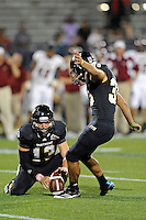 25 October 2011:  FIU kicker Jack Griffin (38), with quarterback Wesley Carroll (13) holding, kicks the game-winning field goal in overtime as the FIU Golden Panthers defeated the Troy University Trojans, 23-20 in overtime, at FIU Stadium in Miami, Florida.