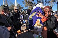 JH04 RAS EL JEDIR (TÚNEZ), 2/3/2011.- Una mujer sudanesa que han huído de Libia pasa al lado de unos guardias fronterizos en el paso fronterizo de Ras el Jedir (Túnez) hoy, miércoles 2 de marzo de 2011. La situación humanitaria en la frontera de Túnez con Libia puede degenerar en una grave crisis si los miles de refugiados egipcios y de otras nacionalidades que llegan a la zona no son pronto repatriados. EFE/Jim Hollander..