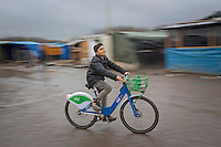 FRANCE, Calais: 18 December 2015 A young refugee boy rides a bike through the refugee camp known as 'The Jungle'. The camp in Calais is now believed to hold 7,000 refugees, who are all trying to prepare for the cold winter months ahead.<br /> Rick Findler / Story Picture Agency