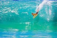 A bodyboarder takes on the large, barreling shorebreak wave at Ke Iki Beach, on the North Shore of Oahu.