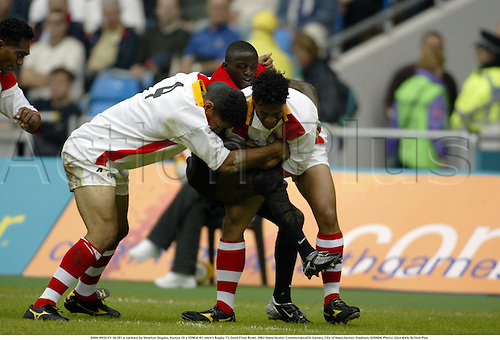JOHN WESLEY 'ALOFI is tackled by Newton Ongalo, Kenya 10 v TONGA 41, Men's Rugby 7's Semi Final Bowl, 2002 Manchester Commonwealth Games, City of Manchester Stadium, 020804. Photo: Glyn Kirk/Action Plus...union.international internationals.sevens 7s.tackle tackling.
