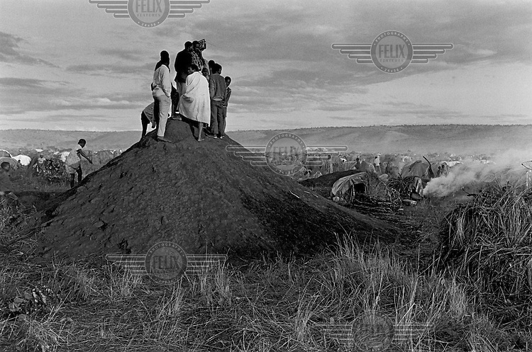 People crowd together on a hill to listen for news from home at the Rosumo Camp, 18 km from the Kagera river, where 150,000 and later 250,000 Rwandan refugees fled the genocide to form what was, in terms of population, the second biggest town in Tanzania.