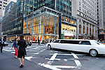 White stretch limousine against office buildings and retail stores. Manhattan, New York, USA