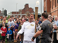 Johnathan Barker of Flintham chats to his polic escort as he carries the Olympic torch at Newark