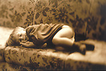 young boy sleeps comfortably on a couch