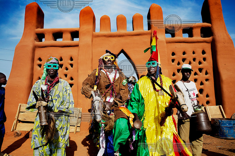 A group of musicians playing beside a mud-faced gateway during the Festival sur le Niger.