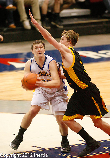 RAPID CITY, S.D. -- Sam Wallin #33 drives on Brady Maxwell #3 of Mitchell during their championship game at the 2012 South Dakota State AA Boys Basketball Tournament in Rapid City, S.D. Saturday (Photo by Dick Carlson/Inertia)