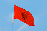 The Albanian flag banner, red with a black double headed eagle, against a blue sky. The Tirana Main Central Square, Skanderbeg Skanderburg Square. Tirana capital. Albania, Balkan, Europe.