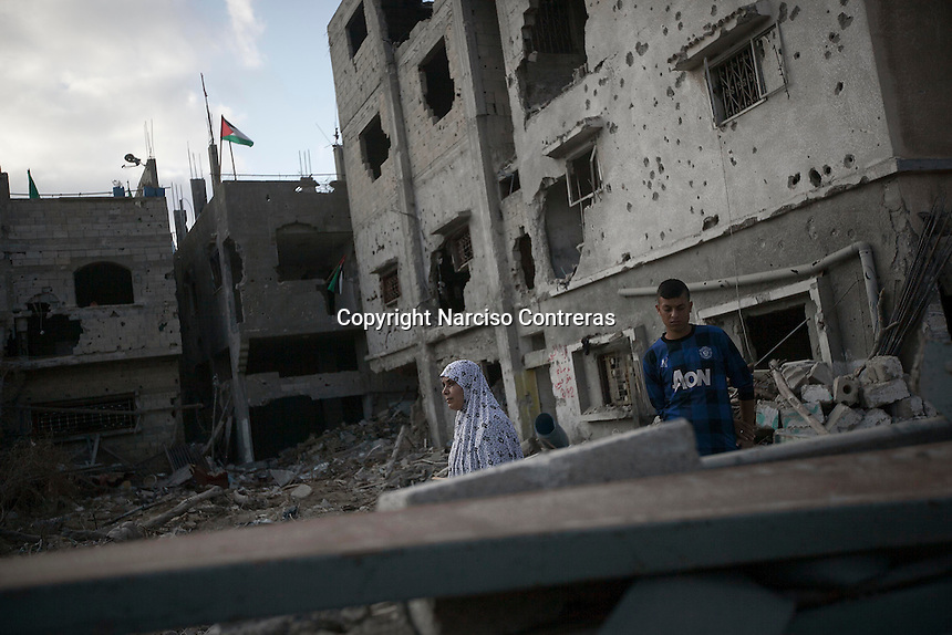 "In this Friday, Aug. 15, 2014 photo, a Palestinian woman walks through what remains from her house as she looks for her belongings after it was destroyed during the ""Protective Edge"" Israeli military operation in Shuyaja neighborhood in Gaza City. After a five days truce was declared on 13th August between Hamas and Israel, civilian population went back home looking for their goods in Gaza Strip. (Photo/Narciso Contreras)"