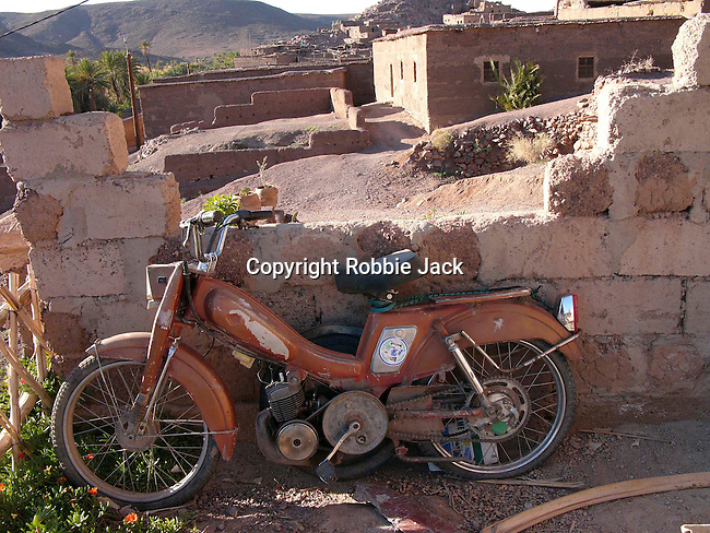 A moped parked against a wall at the oasis at Fint in Morocco.